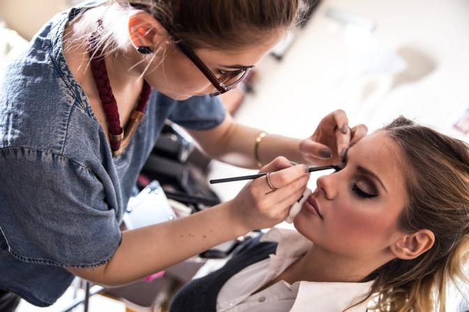 Eine Frau wird von einer Visagistin geschminkt