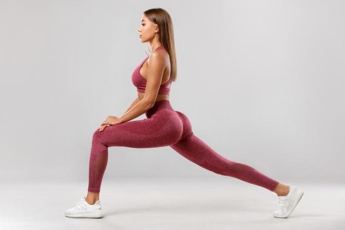 Eine Frau macht als Gleichgewichtsübung einen Ausfallschritt