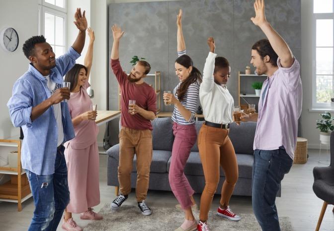 Gruppe junger Leute mit selbstbewusster Ausstrahlung feiert in einer Wohnung.