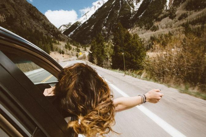 Eine Frau mit wehenden Haaren sitzt in einem Auto und fährt eine Bergstraße entlang
