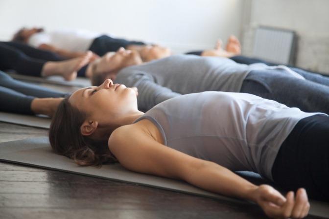 Verschiedene Menschen machen Yoga