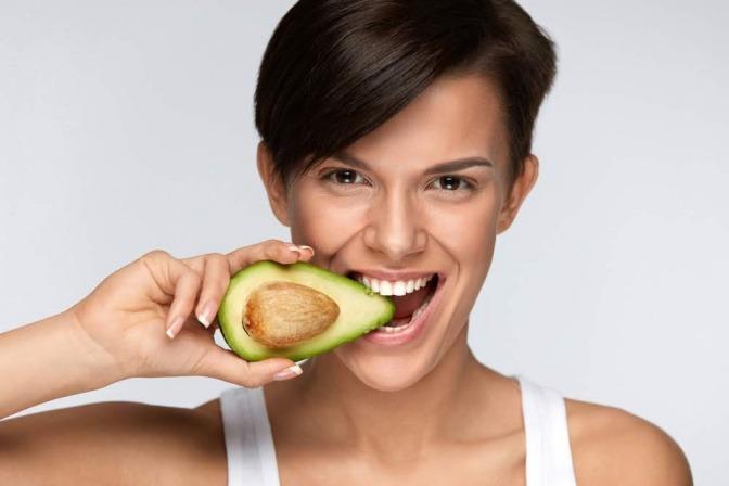 Eine Frau beißt in eine Avocado, die reich an Vitamin B6 ist