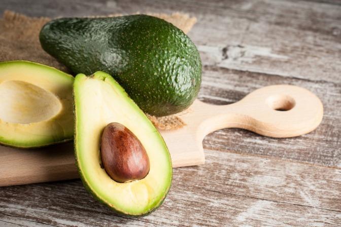 Avocades liegen auf einem Brett