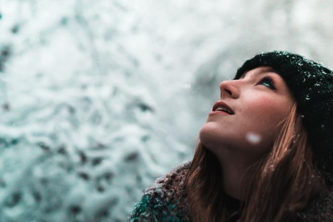 Eine Frau schaut im Winter zum Himmel
