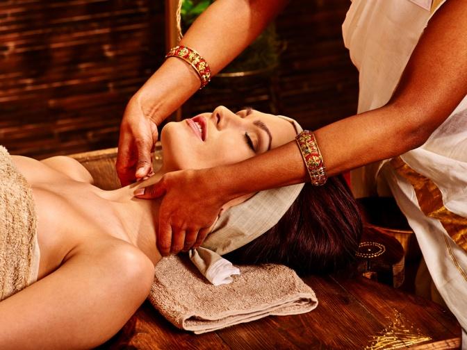 Eine Frau liegt auf dem Rücken und erhält eine Ayurveda Massage
