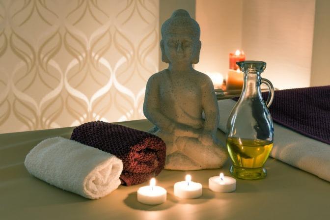 Ayurveda Öl, Statue und Kerzen als Stilleben für Ayurveda-Behandlungen