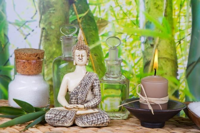 Ayurveda Utensilien liegen neben einer Buddha Statue