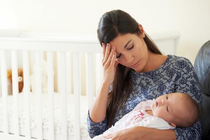 Eine Mutter sitzt mit ihrem Kind neben dem Kinderbett