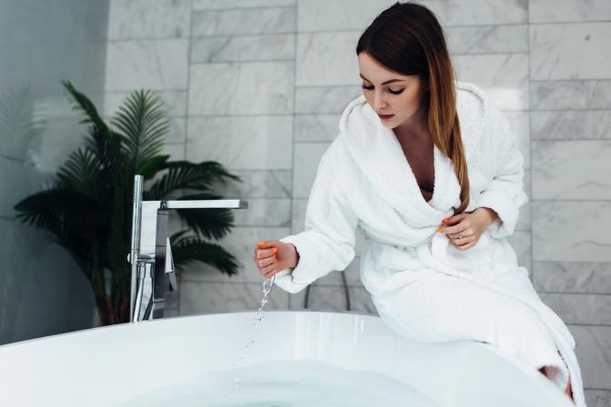 Eine Frau gibt Salz ins Badewasser.