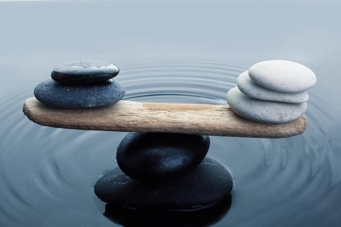 Ausbalancierte Steine auf einem Holzstück im Wasser