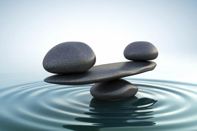 Diverse Steine unterschiedlicher Form und Größe sind vor dem Hintergrund des Meeres sorgfältig aufeinander gestapelt und befinden sich im perfekten Gleichgewicht.