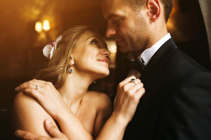Eine Frau ist in einer Ballnacht an einen Mann gelehnt und lächelt