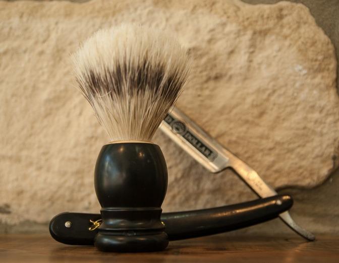 Eine Nahaufnahme eines Rasiermessers und einer Bürste für das Auftragen von Rasierschaum.