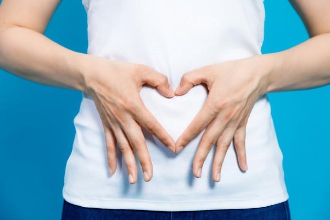 Frau macht mit Händen ein Herz vor dem Bauch