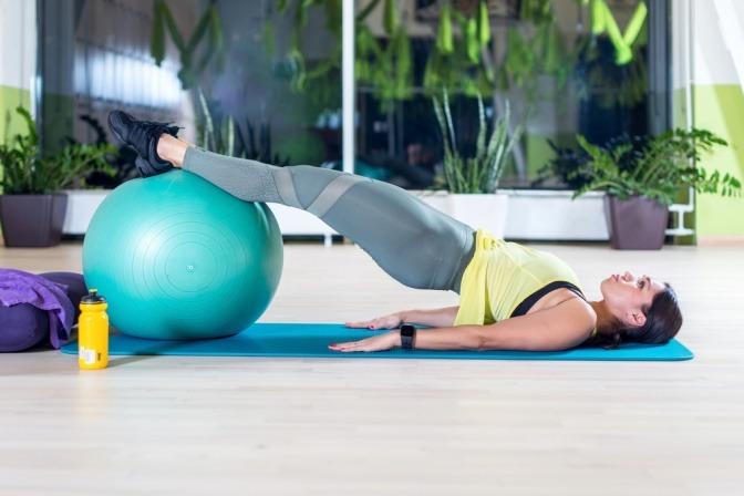 Eine Frau verwendet bei einer Übung beim Beckenbodentraining einen Ball