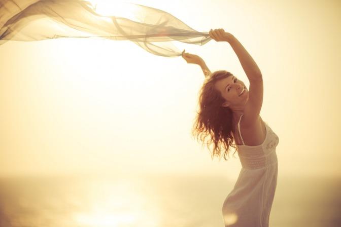 Eine Frau fühlt sich frei und tanzt mit einem fliegenden Tuch