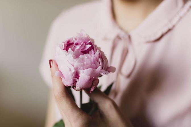 Eine Frau hält eine Blume in der Hand