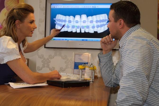 Dr. Klarkowski klärt einen Patienten über Zahnspangen auf
