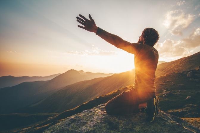 Ein Mann befindet sich auf einem Berggipfel und möchte die Welt umarmen