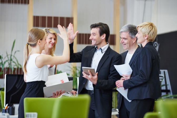 Drei Geschäftsfrauen und zwei Geschäftsmänner stehen beinander im Büro. Eine Frau und ein Mann schlagen ein und symbolisieren damit erfolgreiches weiterkommen.