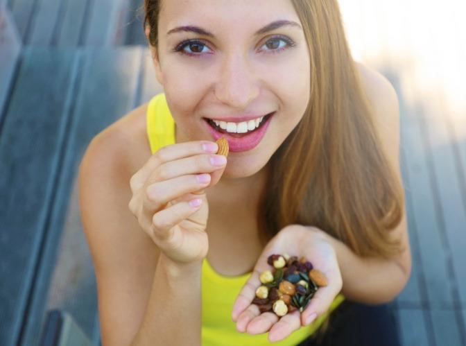 Frau isst beruhigende Lebensmittel (Nüsse)