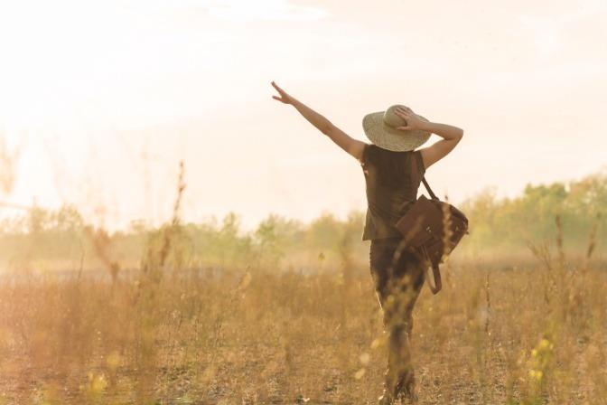 Eine Frau geht über die Wiese und beschließt, glücklich zu sein