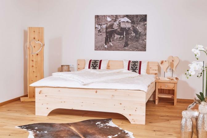 Ein Schlafzimmer mit einem Bett aus Zirbenholz ist aufgeräumt