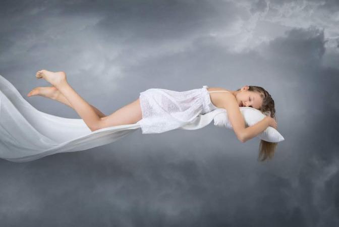 Eine Frau schläft auf einer Wolke