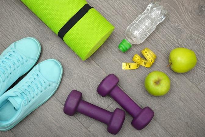 Hanteln, Apfel, Sportschuhe und Maßband