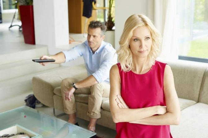 Ein Paar sitzt im Wohnzimmer, sie hat eindeutig Redebedarf, er konzentriert sich jedoch auf den Fernseher.