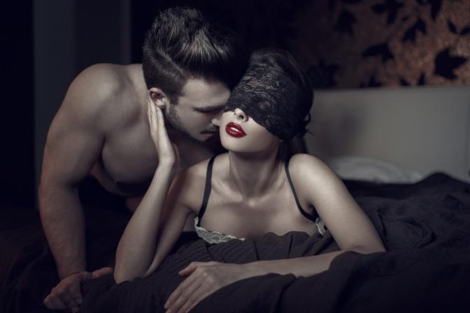 Frau mit Maske in Unterwäsche und jungem Mann