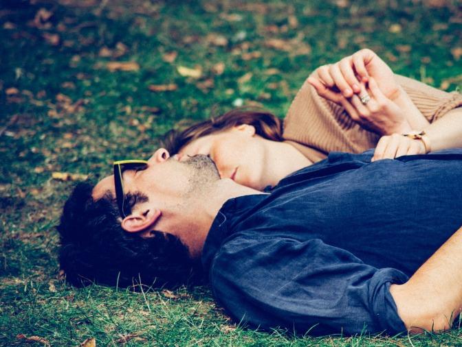 Ein Paar liegt kuschelnd und eng aneinander geschmiegt zusammen auf dem Bett.