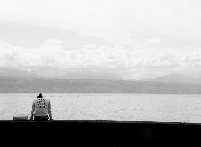 Ein Mann sitzt an einem See. Er trägt einen Pullover mit der Aufschrift Anti Social Social Club.