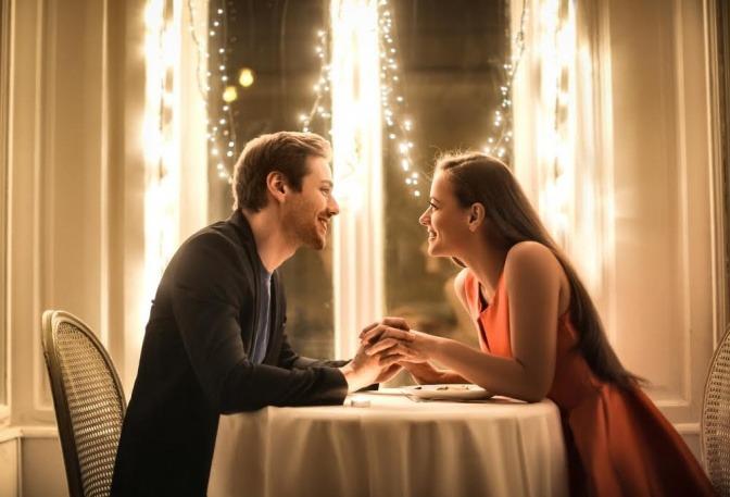 Ein Paar sitzt händchenhaltend bei einem romantischen Dinner.