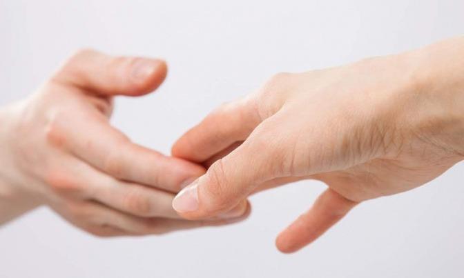 Ein Paar berührt sich mit den Fingerspitzen und ist kurz davor, die Verbindung zu lösen.