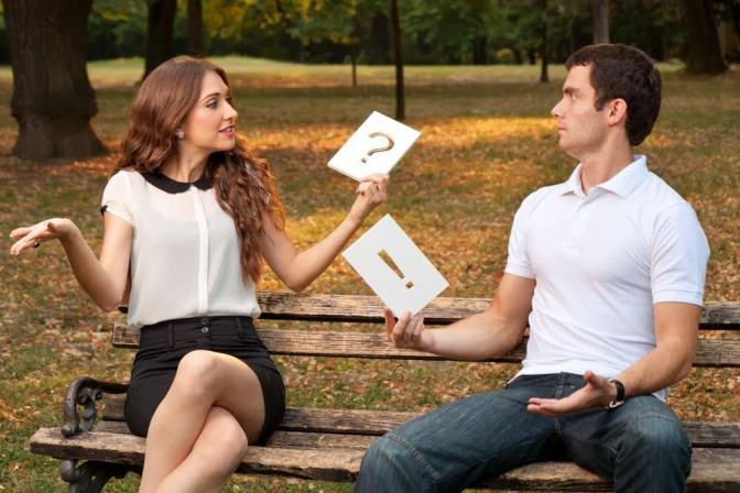 Ein Mann und eine Frau sitzen an entgegengesetzten Enden einer Parkbank, sie schauen sich fragend an. Er hält ein Blatt mit einem Ausrufezeichen in der Hand, sie ein Blatt mit einem Fragezeichen.