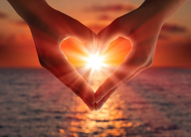 Vor einem romantischen Hintergrund mit einer untergehenden Sonne am Horizont, zeigt das Bild ausschnitthaft die Hände eines Mannes und einer Frau, die gemeinsam ein Herzzeichen bilden.