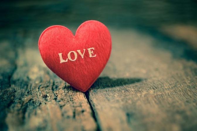 Ein kleines Stoffherz mit dem eingestickten Schriftzug LOVE.