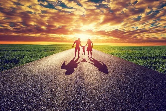 Ein Paar mit Kind geht händchenhaltend dem Sonnenuntergang entgegen.