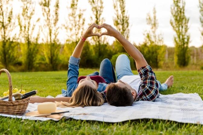 Ein Paar liegt gemeinsam auf der Wiese in einem Wald. Sie formen mit ihren Händen ein Herz und halten es gegen die untergehende Sonne.