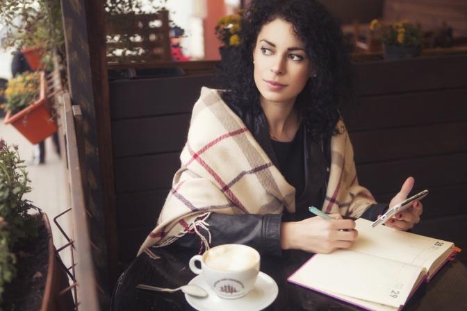Eine Frau sitzt an einem Tisch, vor ihr liegt ein Notizbuch, sie hält ein Smartphone in der Hand. Sie schaut sich nach hinten um. Es wirkt, als überlege sie sich eine Antwort auf einen Test.
