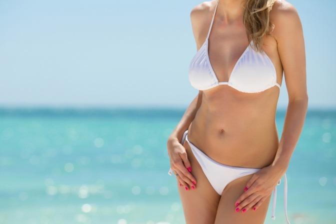 Frau im Bikini am Strand.