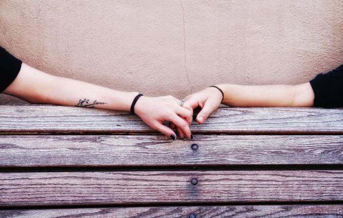 Die Hände eines Paares, das nebeneinander auf einer Parkbank sitzt, liegen auf der oberen Kante der Rückenlehne und berühren sich dabei.