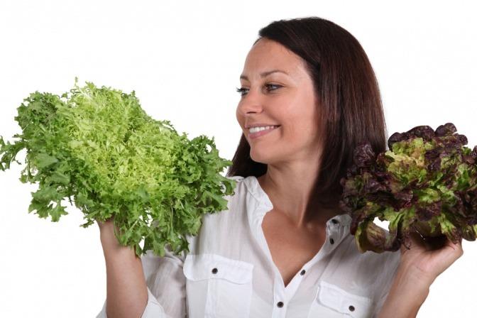 Eine Frau hält verschiedene dunkle Blattgemüse in ihren Händen und lächelt dabei.