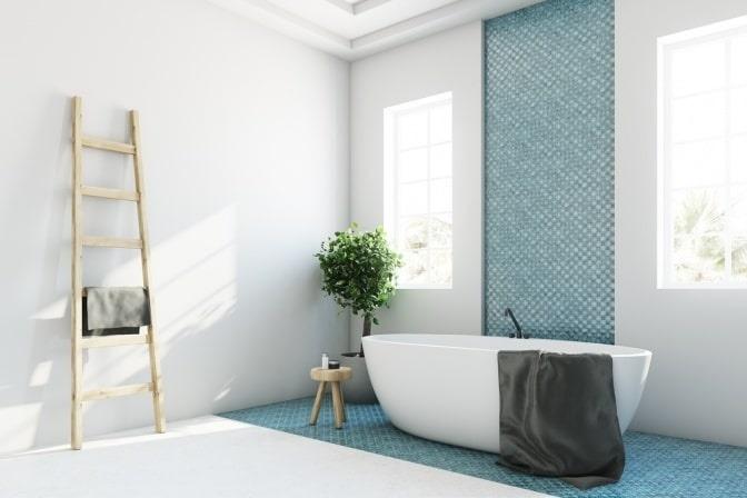 Vor einer blauen Wand steht eine Badewanne