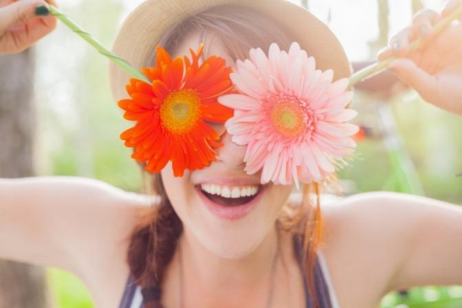 Eine Frau hält glücklich Blumen vors Gesicht