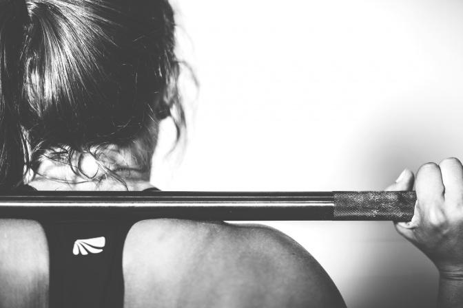 Eine Frau hält beim Bodybuilding eine Stange auf den Schultern