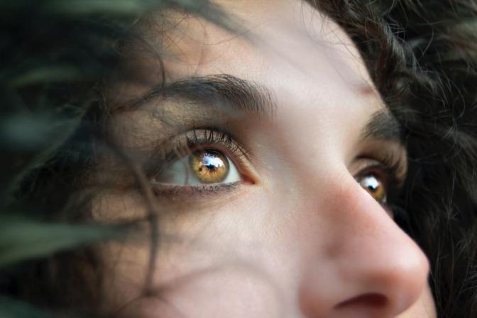 Eine Frau mit Locken hat leuchtende bernsteinfarbene Augen