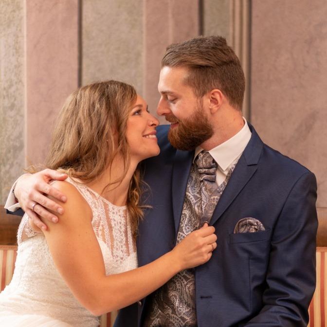 Zwischen einer Braut und einem Bräutigam befindet sich ein Blumenstrauß