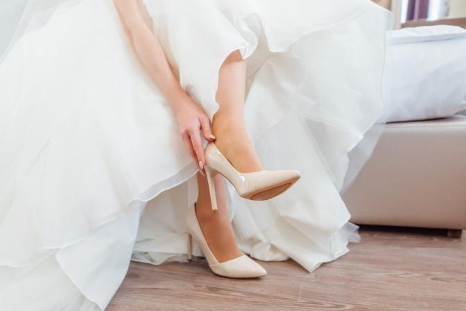 Eine Braut trägt Brautschuhe ivory